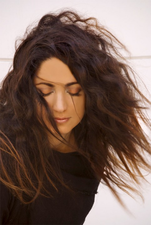 woman with long medium brown hair with her eyes closed