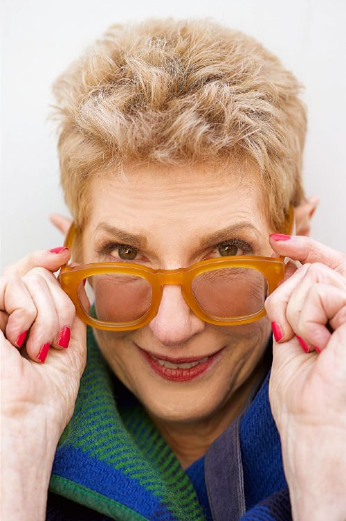 older woman with short strawberry blonde hair smiling and holding her hands onto her large orange glasses
