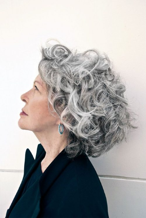 profile of a woman with short wavy gray hair looking up