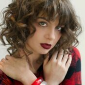 young woman with medium short, curly hair posing with her hands crossed on her shoulders
