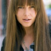 young woman with long straight hair and bangs posing