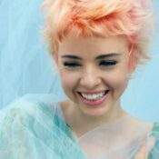 Young woman with wavy short pastel hair smiles and look down
