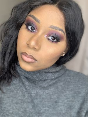 black woman with long hair and strong eye makeup wearing a grey turtleneck