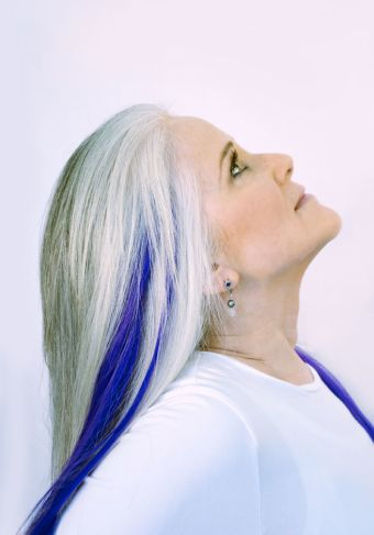 woman with silver hair and blue streaks glancing up from a profile
