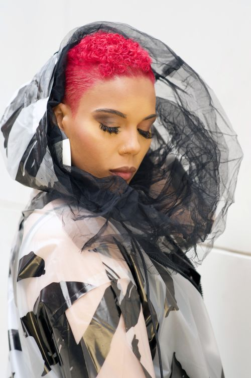 glamorous black woman with vibrant red pixie haircut wearing a coat with tulle collar