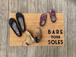 shoes on a mat that says Bare Your Soles