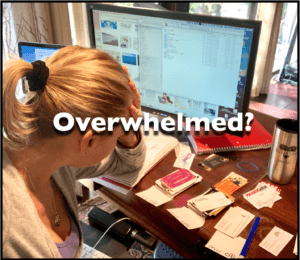 Overwhelmed woman with head in hands sitting at a messy desk and computer