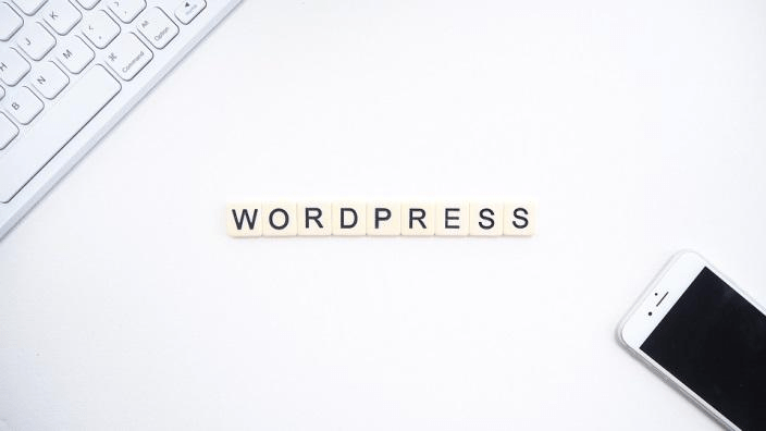"""Letter cubes on a white surface that spell out """"WordPress""""."""