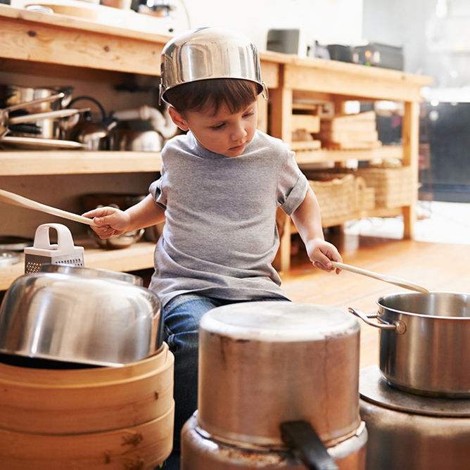 A young boy playing drums on pots and pans