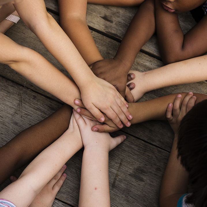 Diverse hands join together on the wooden table
