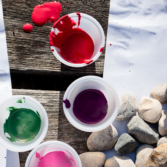 Some cups of paint on a craft table. kids will paint rocks
