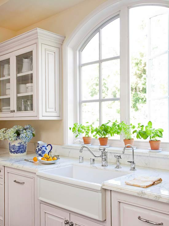 kitchens - wood panel dishwasher white kitchen cabinets marble countertops farmhouse sink potted herbs arched window  BHG  Sunny classic kitchen
