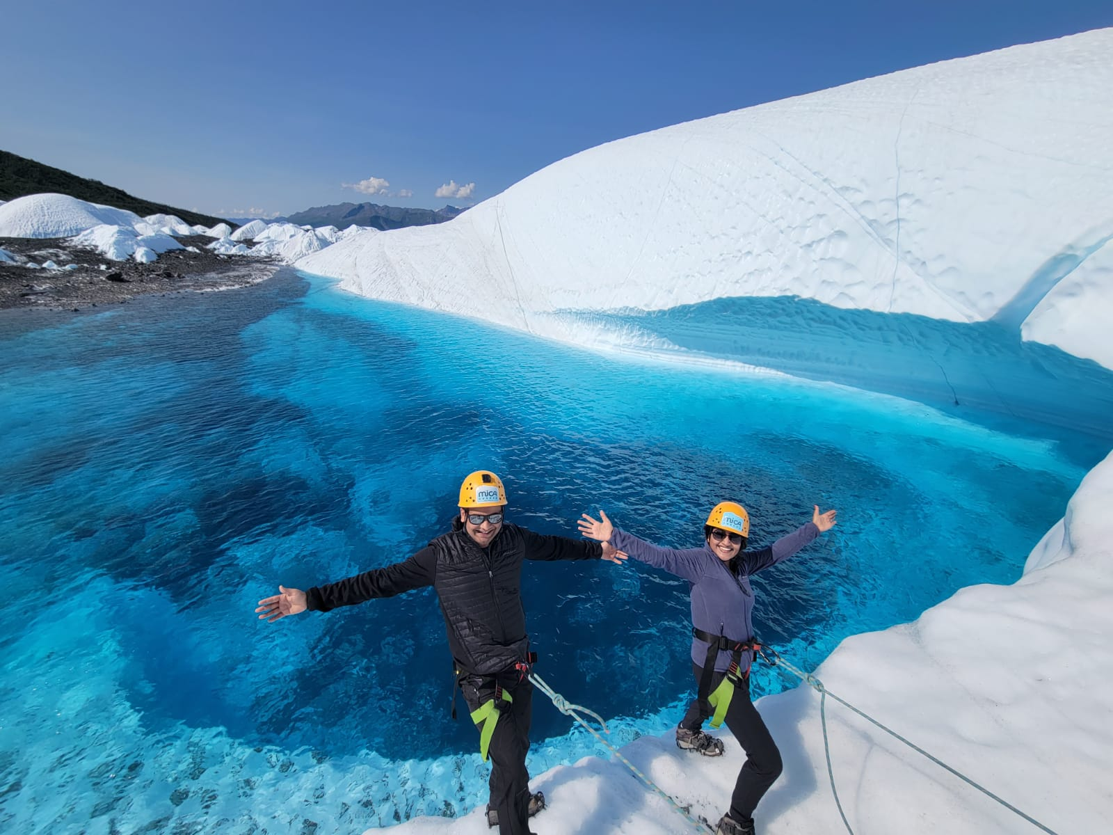 Explorers on ropes over blue glacial lake