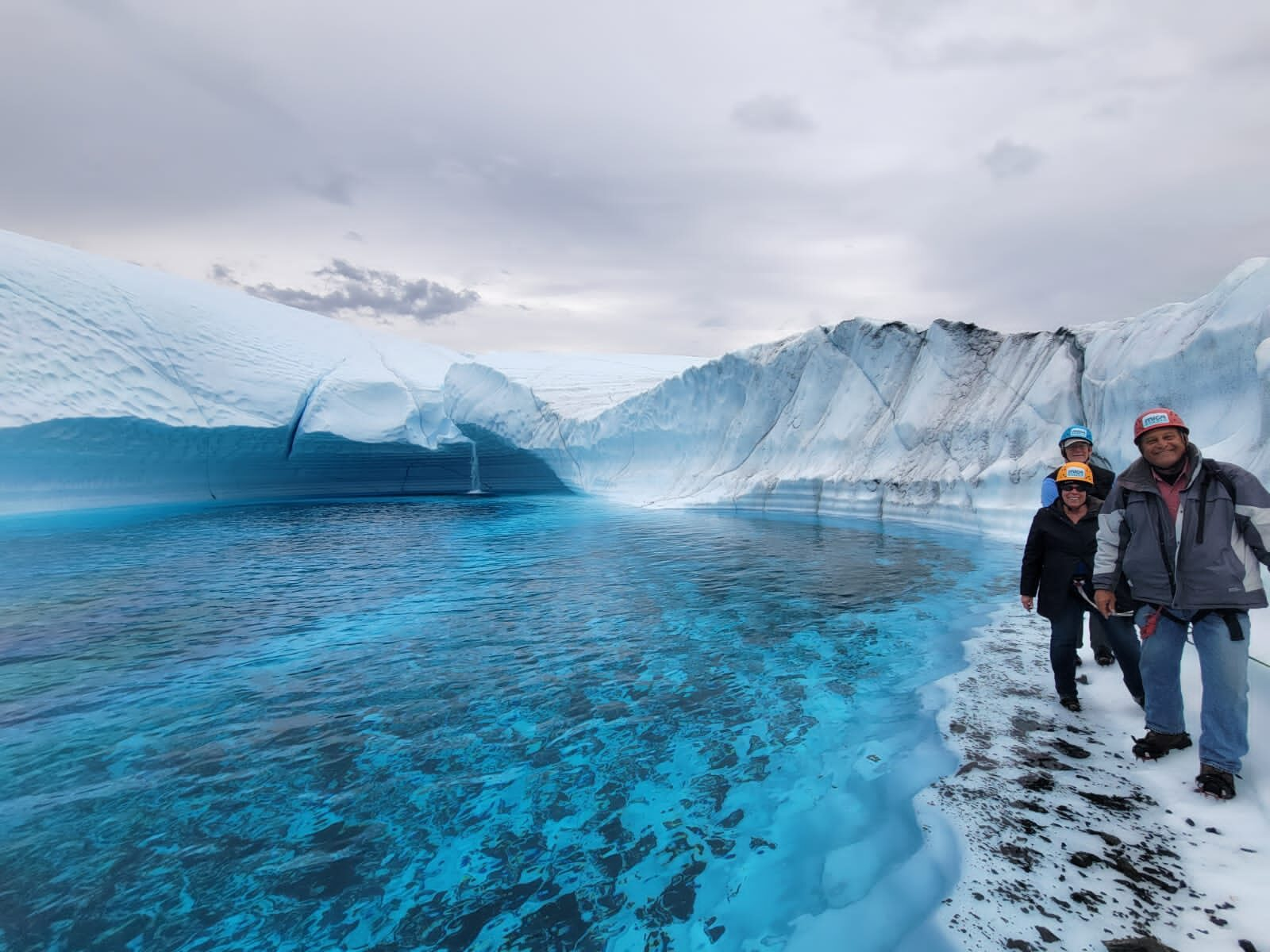 family on ice near blue lake