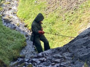 person in raingear holding rope
