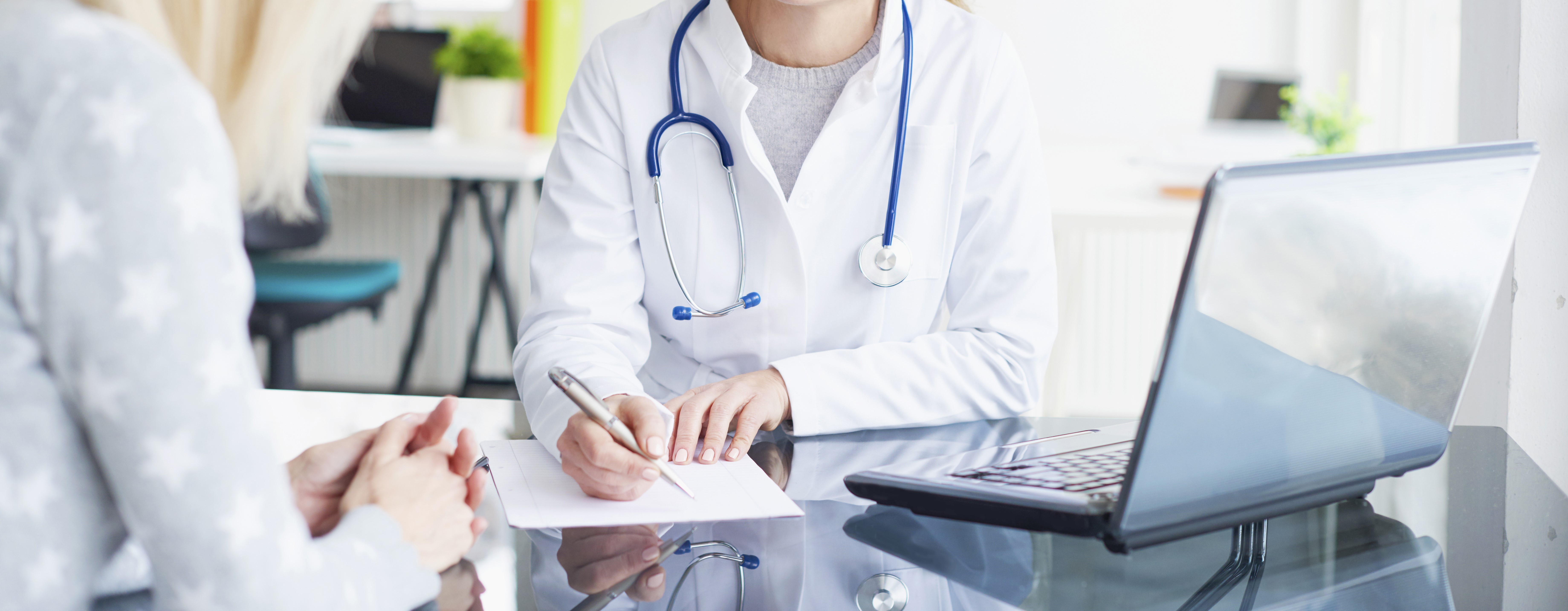 Shot of a middle aged female doctor sitting in front of laptop and consulting with her patient.