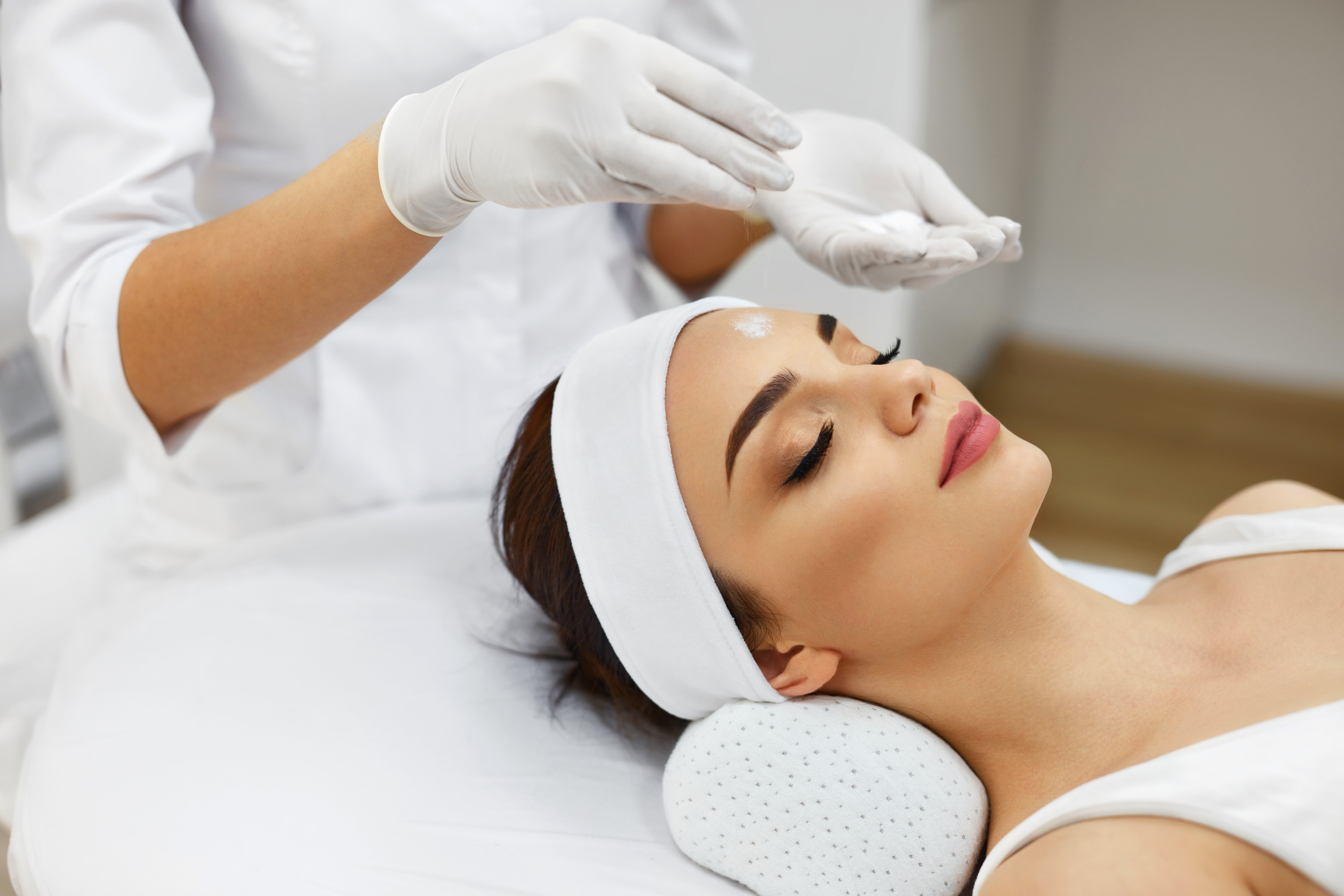Spa Salon. Beautician Does Cosmetic Procedures Applying White Cosmetic Powder On Woman Face. Closeup Of Beautiful Female Receiving Facial Treatment, Cosmetic Procedures. Skin Care. High Resolution