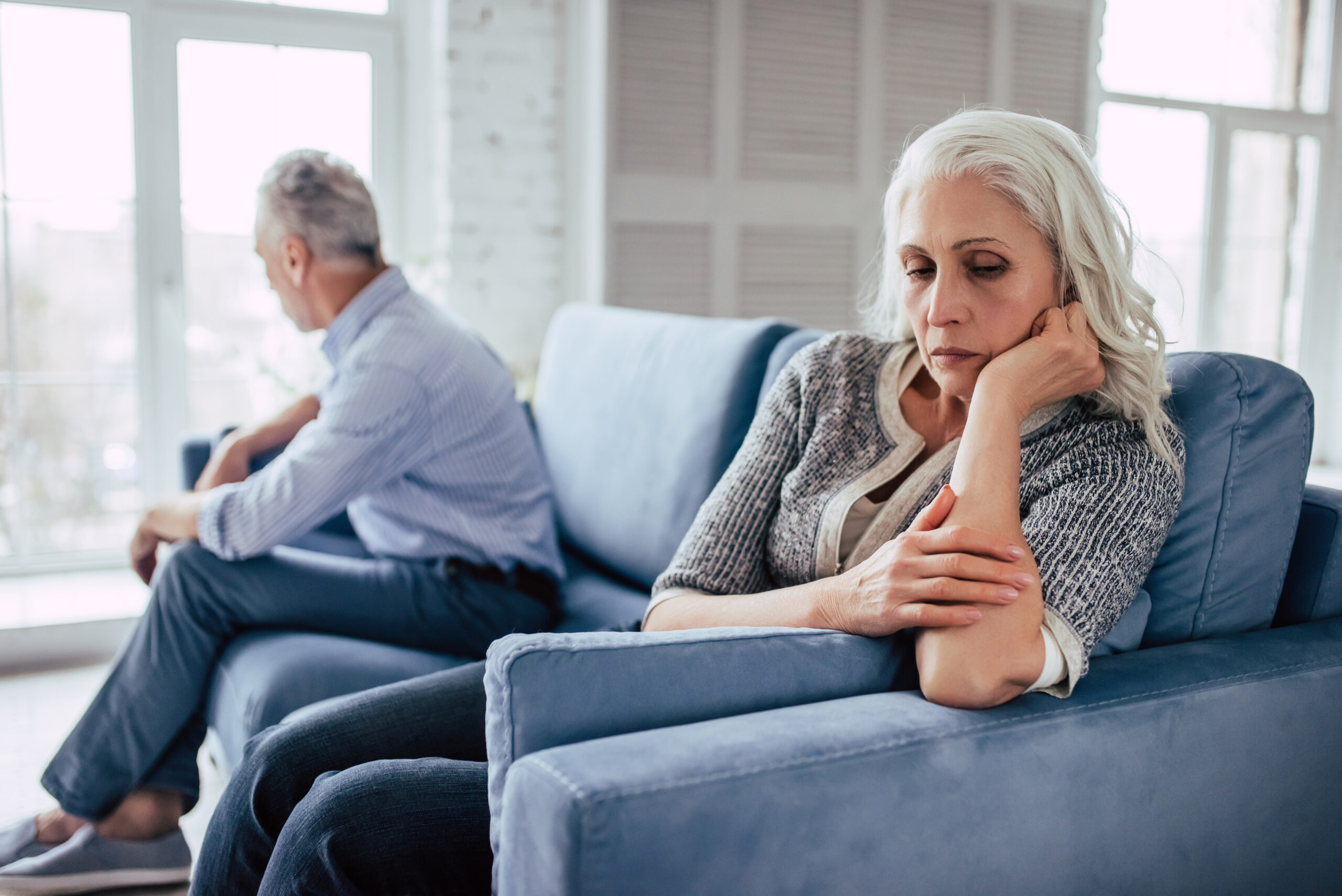 Senior couple at home. Handsome old man and attractive old woman are having relationship problems. Sitting on sofa together and looking to opposite sides.