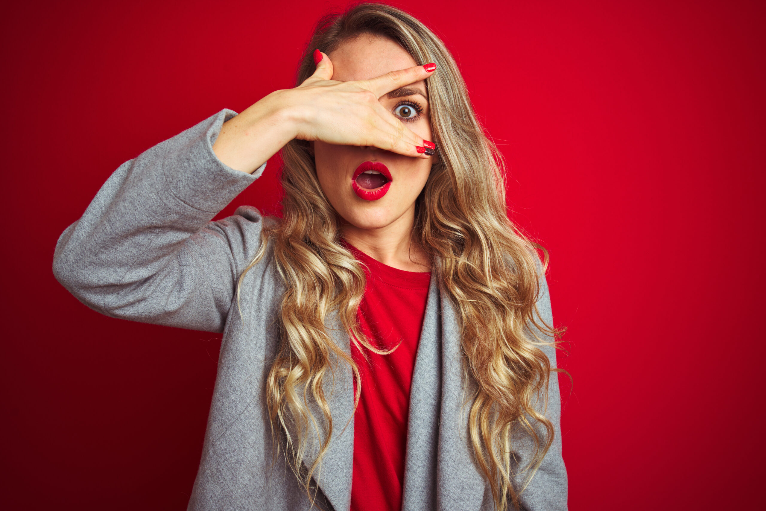Young beautiful business woman wearing elegant jacket standing over red isolated background peeking in shock covering face and eyes with hand, looking through fingers with embarrassed expression.