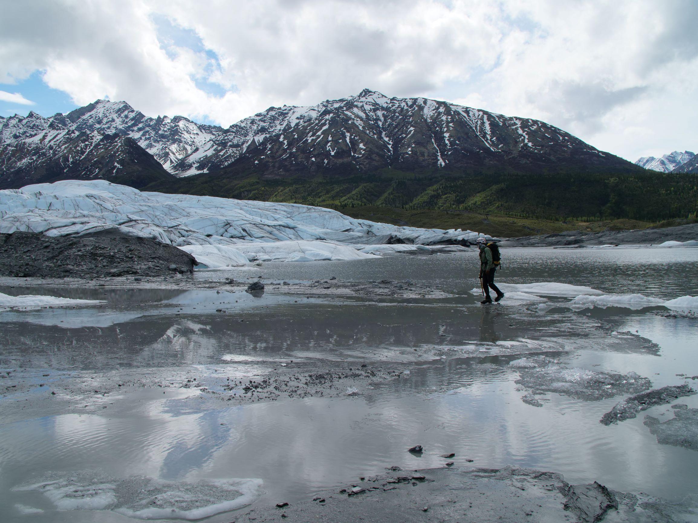 person walking on glacier