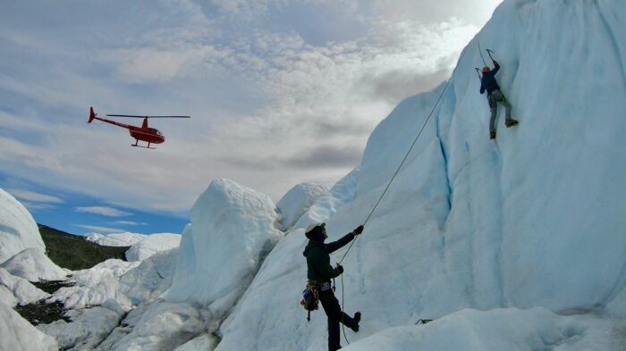 helicopter over glacier and ice climbers