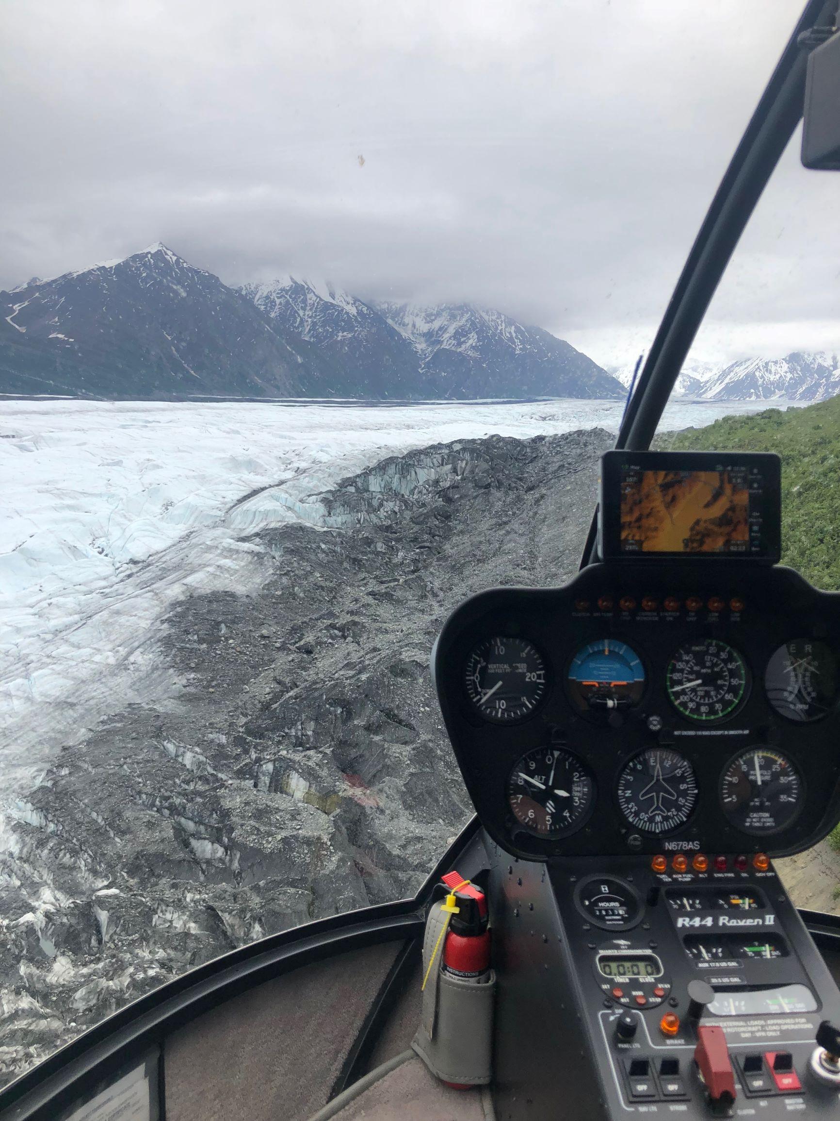 helicopter flying over glacier