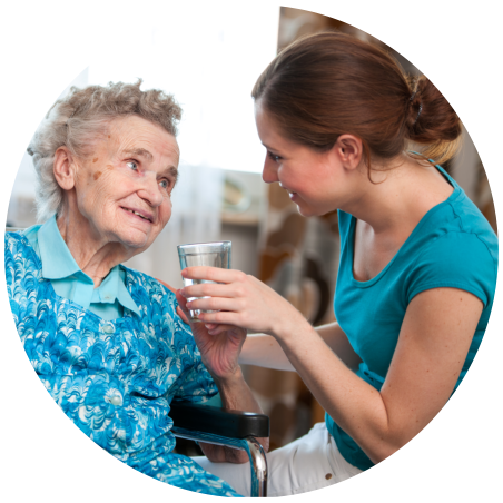 caregiver assisting an old woman to drink water
