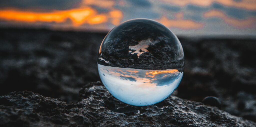 Glass marble globe on the ground with upsidedown sky