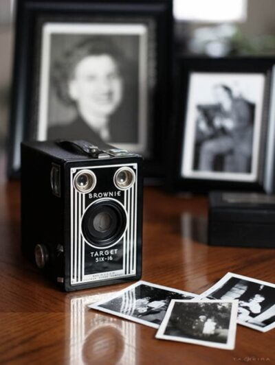 Image of a Kodak Brownie Six-20, the original point & shoot camera, with family pictures.