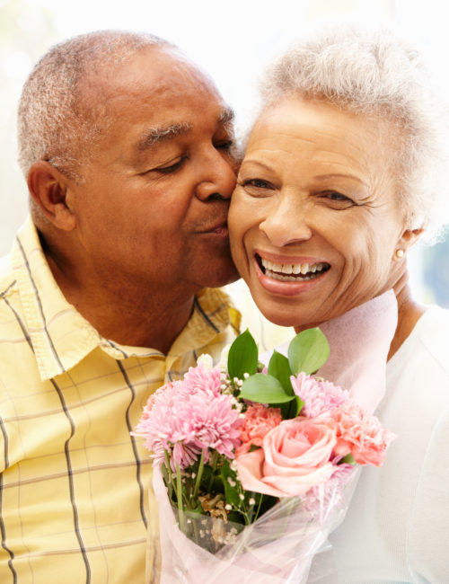 Senior man giving flowers to wife smiling happy at camera