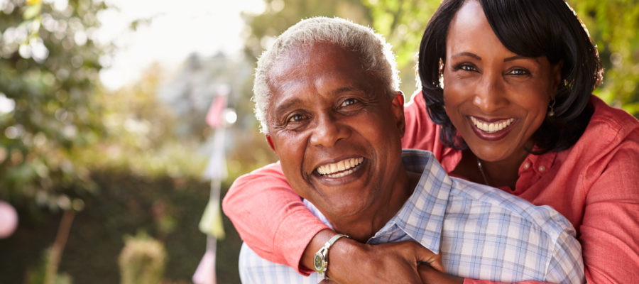 Senior black couple piggyback in garden looking at camera