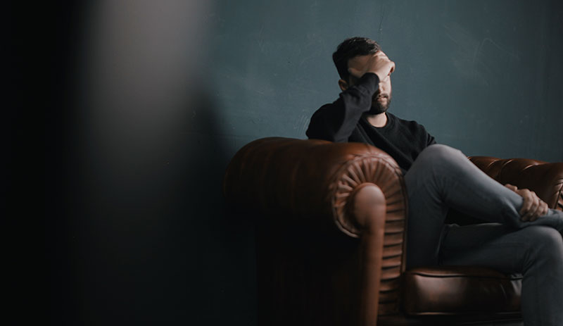 Man sitting on sofa in the dark