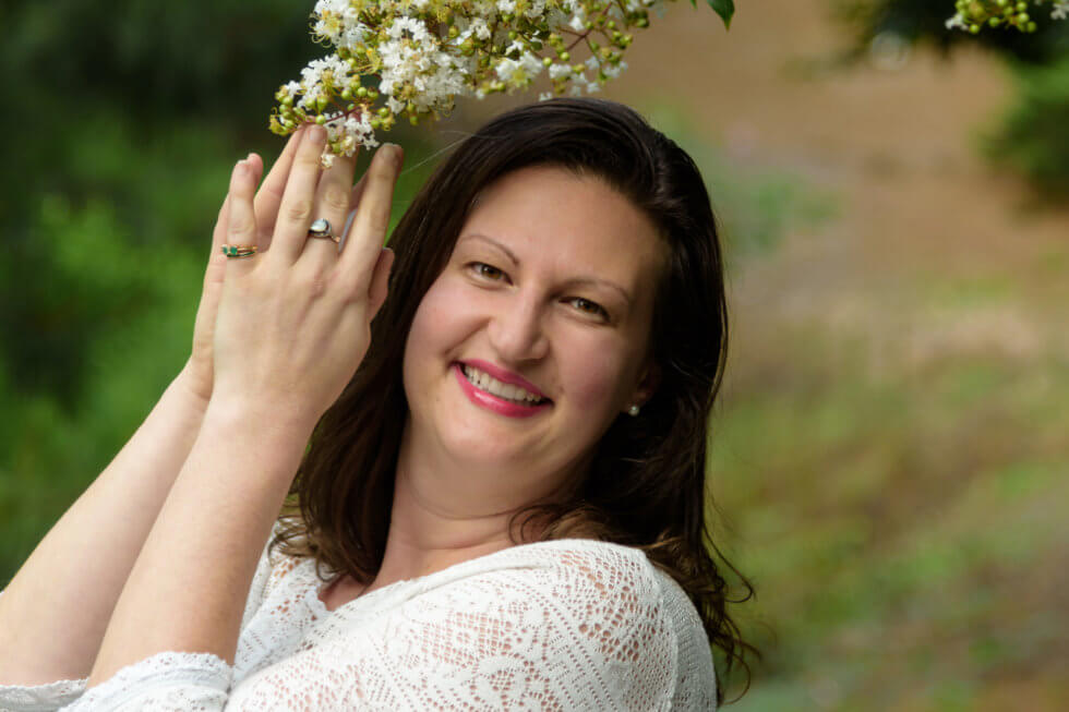 Image of Intuitive Nicole Leffer with hands in prayer under a flowering tree
