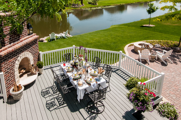 bakyard on a canal, with a grey deck, outdoor table and fireplace.