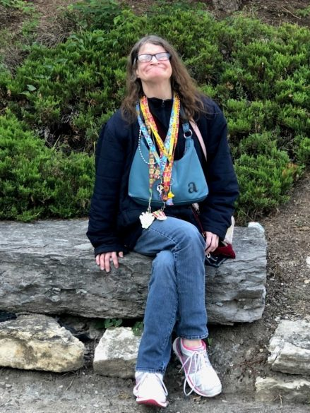 Angee, a woman with long brown hair and eyeglasses wears a navy blue sweater, denim blue jeans, and pink tennis shoes smiles and poses while sitting on a large rock.