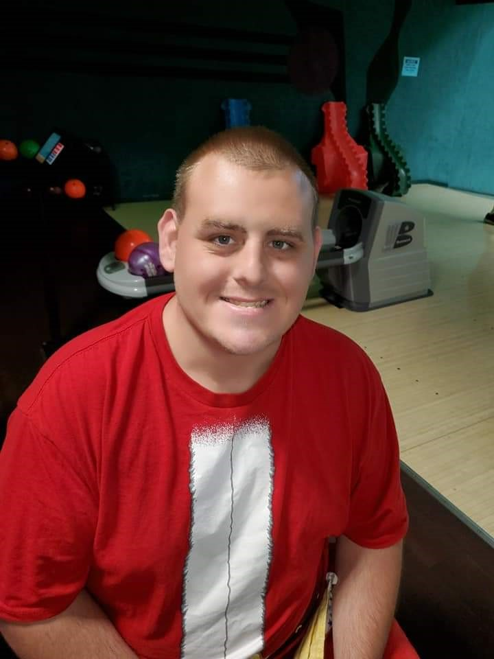 Image of a young man, smiling, wearing a red t-shirt.