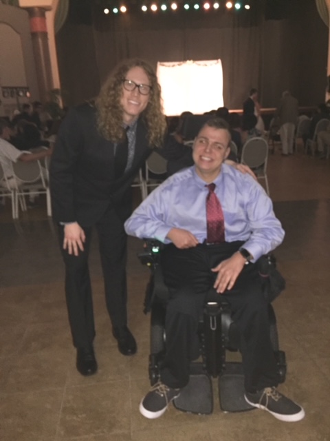 Two men, both dressed in shirt and ties smile for the camera. One of the men has long hair and is standing next to the other that sits in a wheelchair.