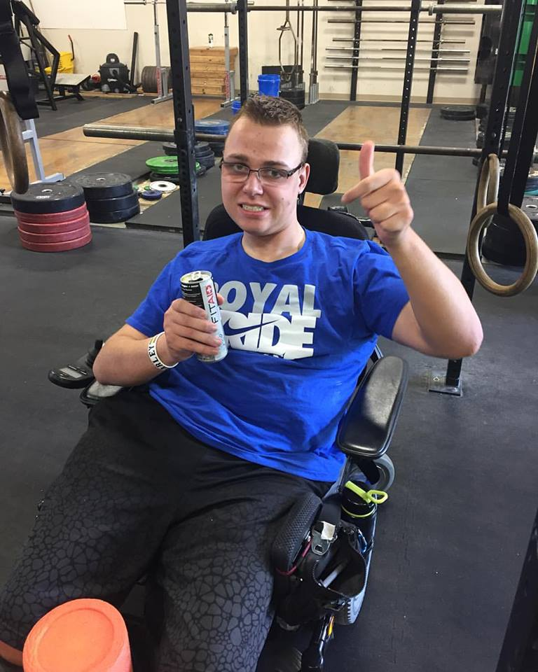 A young man in a weight-lifting gym gives a thumbs-up sign.