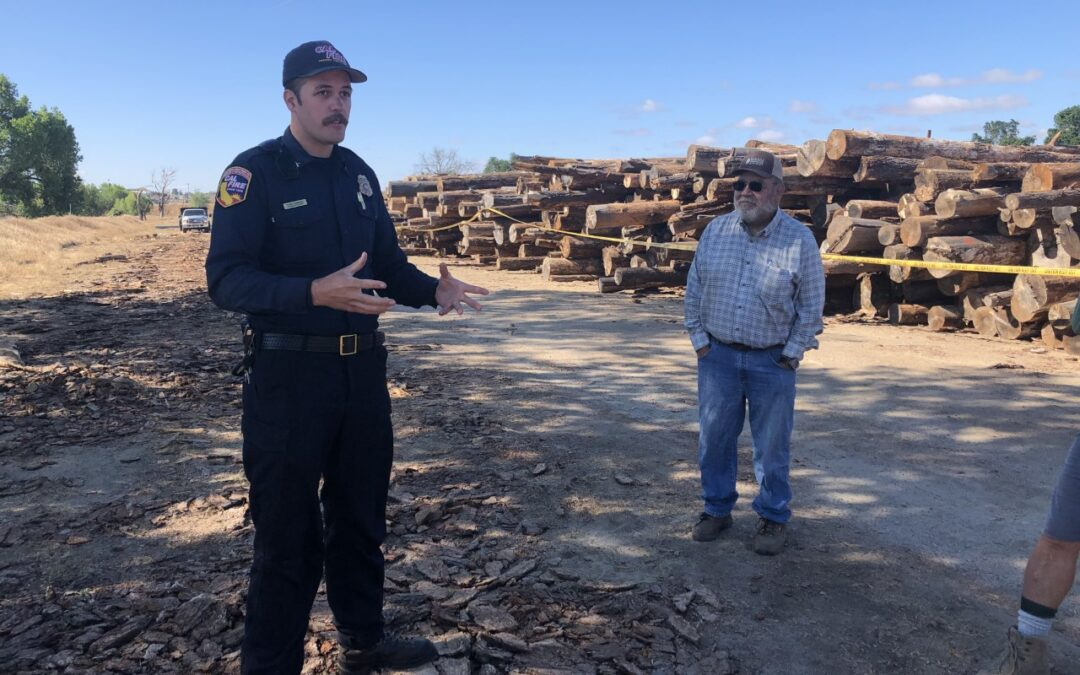 Cal Fire employee with SRCD board member at River Conservancy Location of log decks. Log decks stacked in background.