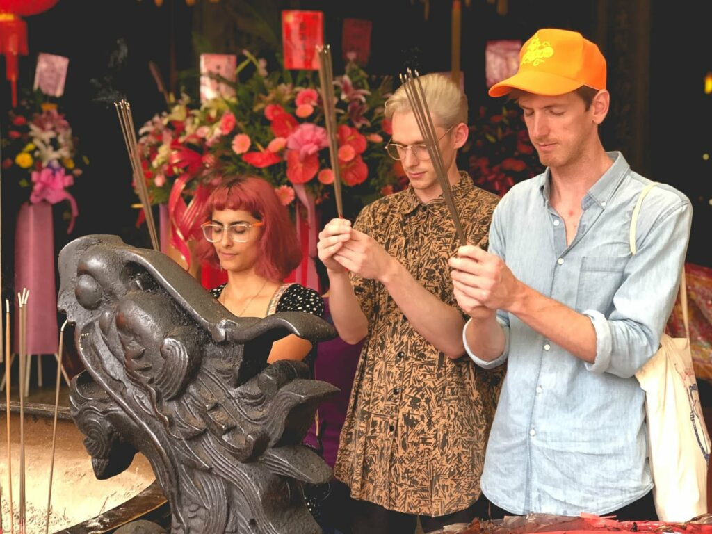 Michelle, Taylor and Peter holding incense.