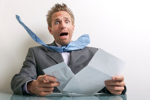 Shocked,Businessman,Opening,A,Letter,With,A,Wide-eyed,Gasp,Of