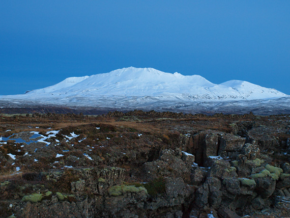 barren landscape with snow covered mountain in the background