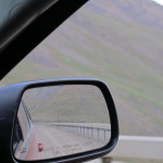 """Looking back in the passenger side mirror at the """"guard rail""""."""