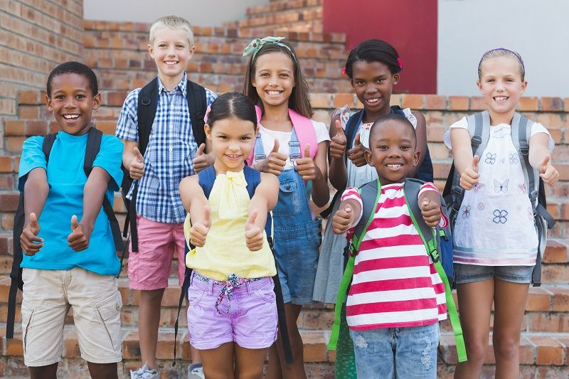 Group-of-kids-standing-on-staircase-showing-thumbs-up-comp
