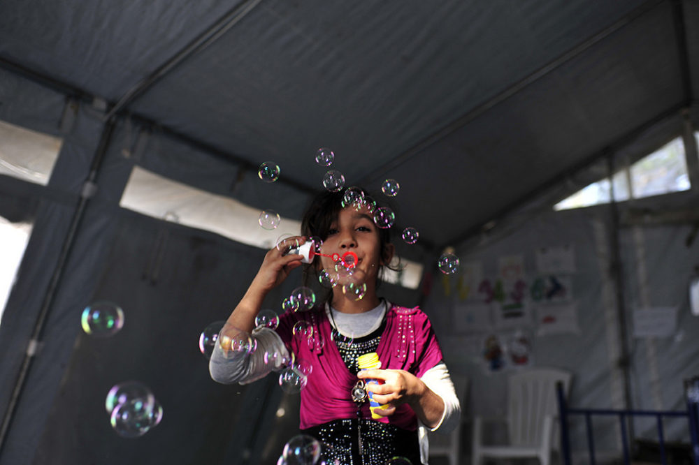 Mashable screen capture - refugee girl blowing bubbles in Serbia.