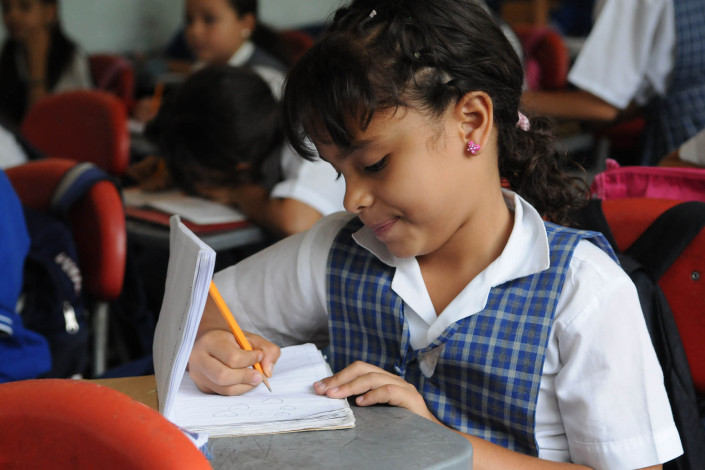 A 7-year-old girl writes in her Spanish notebook in a classroom in Medellín, Colombia.