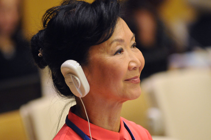 A woman wearing headphones listens at a meeting at the UN.
