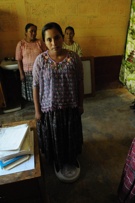 An indigenous Mayan woman, 7 months pregnant, is weighed at a health center in rural Guatemala.
