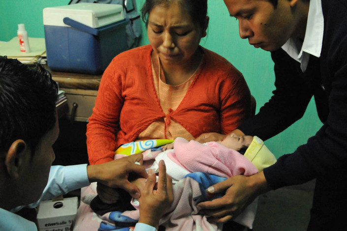 An indigenous Mayan woman winces as her 2-month-old daughter cries as she receives a rotavirus vaccination injection at a health center in rural Guatemala.