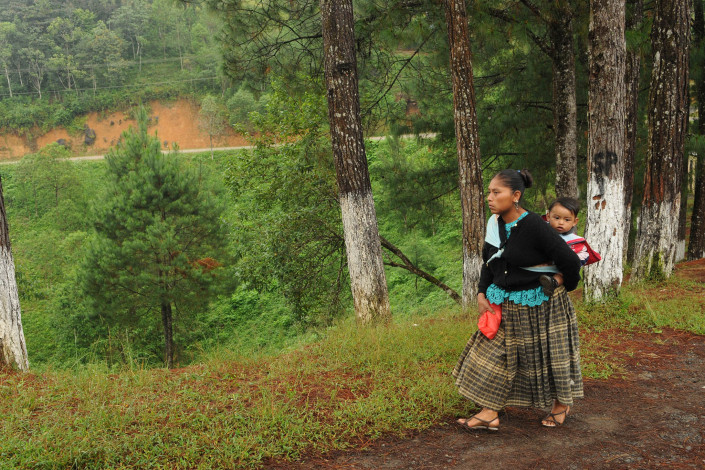 An indigenous Mayan woman walks up steep mountainous terrain with her 18-month-old son on her back, for a health checkup at a rural clinic in Sacanilla, Guatemala.